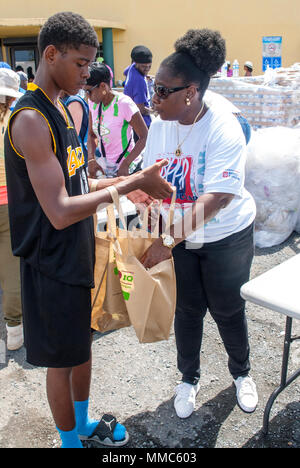 Kimari McIntosh, member of the Allen D. Burke Foundation, volunteers to fills bags with emergency relief supplies to be distributed to the community, October 9, 2017, St. Croix, U.S. Virgin Islands.  The Allen D. Burke Foundation is a local non-profit organization that mentors adolescence boys through athletics and community service.  (Mississippi National Guard photo by Spc. Jovi Prevot, 102d Public Affairs Detachment) - Stock Photo