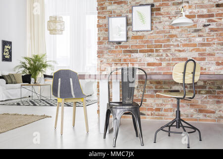 New loft interior with brick wall, table, chairs and sofa - Stock Photo