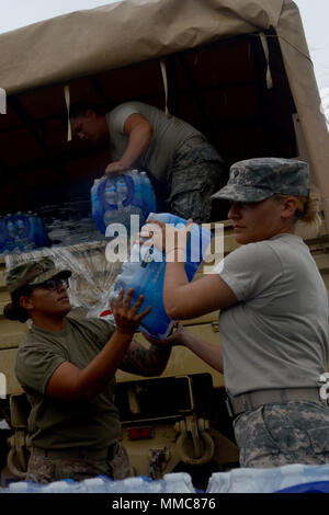 Sgt. Ashley Green, a Juana Diaz, Puerto Rico, native and human resource noncommissioned officer; and Spc. Ambar Rodriguez, a Ponce native and petroleum supply specialist, 393rd Combat Sustainment Support Battalion, 166th Regional Support Group, 1st Mission Support Command, unload water during a commodities delivery in Adjuntas, Oct. 11, 2017. Soldiers assisted FBI agents to deliver food, water and tarps to residents in remote areas near Adjuntas. Government agencies joined efforts to provide disaster relief after Hurricane Maria caused catastrophic damage. (U.S. Army photo by Staff Sgt. Elvis) - Stock Photo