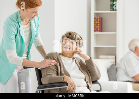Woman on wheelchair looking at her young nurse - Stock Photo
