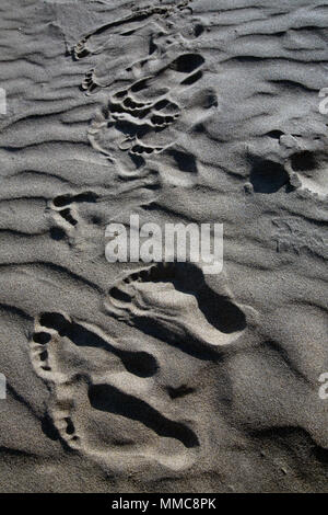 Footprints in the sand of an english beach, late afternoon on a summer family  holiday, long shadows across the ripples in the sand, Sandown, England. - Stock Photo