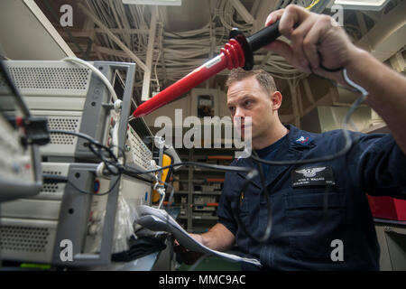 171011-N-ZS023-004 5TH FLEET AREA OF OPERATIONS (Oct. 11, 2017) Aviation Electronics Technician 2nd Class Peter Wallace, a native of Webster, Massachusetts, assigned to the aircraft intermediate maintenance department aboard the amphibious assault ship USS America (LHA 6), calibrates electronic gear in the ship's calibration shop. America is the flagship for the America Amphibious Ready Group and, with the embarked 15th Marine Expeditionary Unit, is deployed to the U.S. 5th Fleet area of operations in support of maritime security operations to reassure allies and partners and preserve the free - Stock Photo