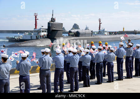 171013-N-TB148-050 BUSAN, Republic of Korea (Oct. 13, 2017).The Ohio-class guided-missile submarine USS Michigan (SSGN 727) (Gold) pulls into the pier of Republic of Korea's Busan Naval Base as part of a routine port visit. The visit is to strengthen the already strong relationship between the U.S. Navy and the people of the Republic of Korea. (U.S. Navy photo by Mass Communication Specialist Seaman William Carlisle) - Stock Photo