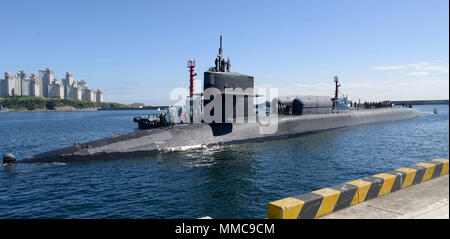 171013-N-TB148-070 BUSAN, Republic of Korea (Oct. 13, 2017).The Ohio-class guided-missile submarine USS Michigan (SSGN 727) (Gold) pulls into the pier of Republic of Korea's Busan Naval Base as part of a routine port visit. The visit is to strengthen the already strong relationship between the U.S. Navy and the people of the Republic of Korea. (U.S. Navy photo by Mass Communication Specialist Seaman William Carlisle) - Stock Photo