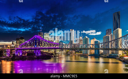 Vibrant night time and day time panorama of Brisbane city with purple lights on Story Bridge, Australia - Stock Photo