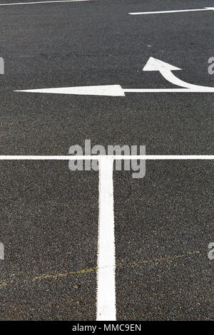 An abstract arrangement for white lines and arrows on the black tarmac of a car park Sandown Isle of White, UK. - Stock Photo