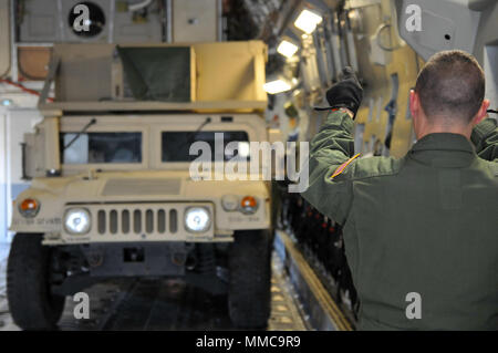An Airman guides an Ohio Army National Guard Humvee onto a C-17 Globemaster III Oct. 11, 2017, at Rickenbacker Air National Guard Base in Columbus, Ohio. About 40 Soldiers from the 137th Signal Company, based in Newark, Ohio, are deploying to Puerto Rico to provide communications support to hurricane relief efforts. (Ohio National Guard photo by 1st Lt. Aaron Smith) - Stock Photo