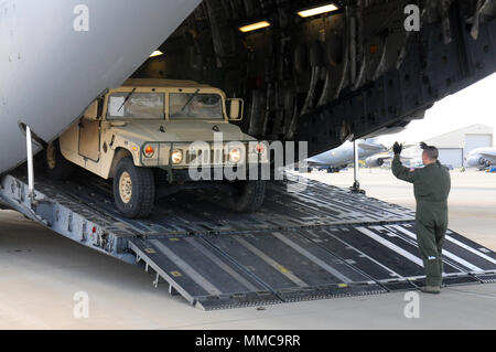 An Airman guides an Ohio Army National Guard Humvee onto a C-17 Globemaster III Oct. 11, 2017, at Rickenbacker Air National Guard Base in Columbus, Ohio. About 40 Soldiers from the 137th Signal Company, based in Newark, Ohio, are deploying to Puerto Rico to provide communications support to hurricane relief efforts. (Ohio National Guard photo by 1st Lt. Jordyn Sadowski) - Stock Photo