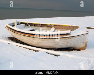 A rowing boat on the beach at Hove sussex england UK covered in snow after a freezing morning white snowfall the sea in cold english winter xmas - Stock Photo