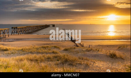 The Headland, Hartlepool, County Durham, England, UK. 11th May, 2018. Weather: A glorious sunrise over Steetley pier at Hartlepool on a bright but chilly Friday morning on the Durham Heritage coast. The pier was used to pump water to long closed and demolished Steetley Magnesite works. Credit: ALAN DAWSON/Alamy Live News - Stock Photo