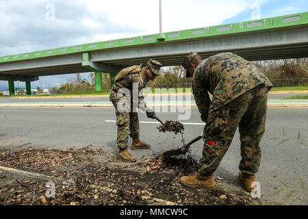 U.S. Marine Corps Lance Cpl. Caesar Rodriguez, left, and Lance Cpl. Javier Reyes, landing support specialists with Detachment 1, Landing Support Company, Combat Logistics Regiment 45, 4th Marine Logistics Group, volunteering with the 26th Marine Expeditionary Unit (MEU), shovel debris from a roadway during road clearance operations in Ponce, Puerto Rico, Oct. 7, 2017. The 26th MEU, along with local authorities and other Department of Defense services, is supporting the lead federal agency, Federal Emergency Management Agency, in providing hurricane relief efforts for Puerto Rico. (U.S. Marine  - Stock Photo
