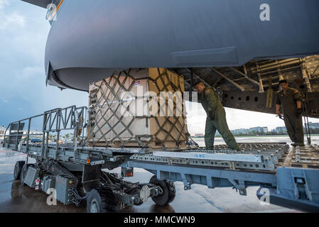 Loadmasters from the Hawaii Air National Guard dowload relief supplies from their C-17 aircraft at Luis Muñoz Marín International Airport in San Juan, Puerto Rico, in the wake of Hurricane Maria Oct. 6, 2017. An aerial port of debarkation at the airport has processed more than 7.2 million pounds of cargo and humanitarian aid since Sept. 23. (U.S. Air National Guard photo by Lt. Col. Dale Greer) - Stock Photo