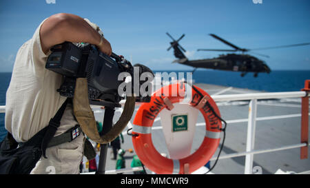 171014-N-MU198-049 CARIBBEAN SEA (Oct. 14, 2017)  CNN affiliates report from the flight deck of the Military Sealift Command hospital ship USNS Comfort (T-AH 20) as a U.S. Army UH-60 Black Hawk helicopter assigned to C Co., 6th Battalion, Combat Aviation Brigade, lands on the flight deck of in order to complete day landing qualifications (DLQ). Comfort is operating in the vicinity of San Juan, Puerto Rico, to provide medical services with additional visits being planned around the island. The U.S. Health and Human Services and Puerto Rico Department of Health representatives are prioritizing p - Stock Photo