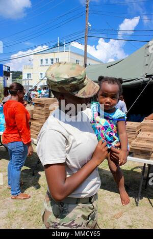Spc. D'Nia Stevens, a member of the Virgin Islands National Guard offers aid to people receiving tarps, non-perishable food, water, hygiene products and other specialty items at a St. John school which serves a point of distribution. St. Thomas and St. John were devastated by both Hurricanes Irma and Maria. In addition to providing relief at points of distribution, National Guard engineers and MPs also provide support on roadways. - Stock Photo