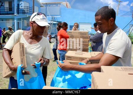 Spc. Jernings Abraham, a member of the Virgin Islands National Guard, offers aid and encouragement to people receiving tarps, non-perishable food, water, hygiene products and other specialty items. St. Thomas and St. John were devastated by both Hurricanes Irma and Maria. - Stock Photo