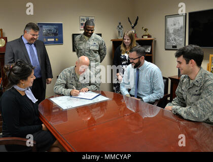 Col. Roman L. Hund, installation commander, signs a proclamation designating October as National Disability Employment Awareness Month in the Brown Building Oct. 10, while Daniela Procopio, Tom Fredericks, Chief Master Sgt. Henry Hayes, Kelly Sullivan, Brian Davies and 2nd Lt. Ben Black look on. Celebrated each October, NDEAM highlights the many contributions of American workers with disabilities and reaffirm the skills and talents they bring to today's workplace. (U.S. Air Force photo by Linda LaBonte Britt) - Stock Photo