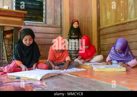 Krabi, Thailand - May 2, 2015: Cute Muslim girls drawing pattern on Batik fabric for painting in their home in Krabi, Thailand - Stock Photo