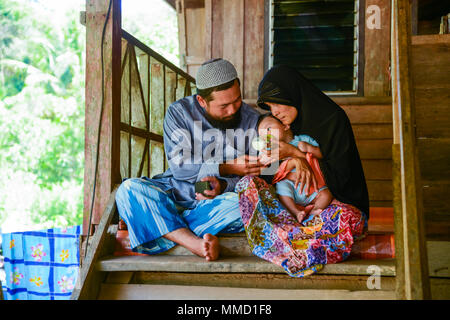 Krabi, Thailand - May 2, 2015: Muslim family feeding milk to their child together in their home in Krabi, Thailand - Stock Photo