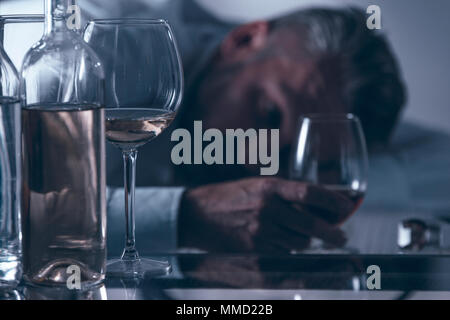 Close-up of a drunken desperate middle-aged man leaning on the table behind bottles and glasses with alcohol - Stock Photo