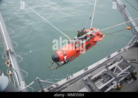171018-N-IO414-023  BUSAN, Republic of Korea (Oct. 17, 2017) Sailors assigned to the Avenger-class mine countermeasures ship USS Chief (MCM 14) lower a mine neutralization vehicle into the water during Multinational Mine Warfare Exercise. The mine countermeasures exercise between the U.S., Republic of Korea, and U.N. Command Sending States is designed to increase combined capabilities and readiness to respond to any contingency on the Korean peninsula. (U.S. Navy photo by Mass Communication Specialist 2nd Class Jordan Crouch/Released) - Stock Photo