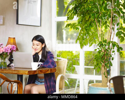beautiful young asian woman sitting in the corner of coffee shop working using laptop computer. - Stock Photo