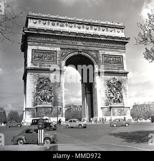 1950s, historical picture of motor vehicles of the day going around the Arc de Triomphe the massive triumphal arch in Paris, France, commissioned by Napoleon in 1806 to celebrate French military victories. - Stock Photo