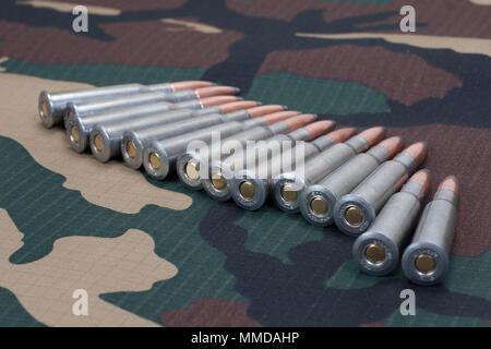 7.62 cartridges on camoflage background - Stock Photo