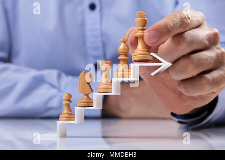 Businessman Placing Wooden King Chess Piece On Top Of Increasing Zigzag White Arrow On Table - Stock Photo