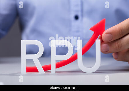 Businessman Holding Red Increasing Arrow Of Revenue Per User On Office Desk - Stock Photo