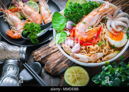 Hot seafood noodle in white bowl on wooden table - Stock Photo