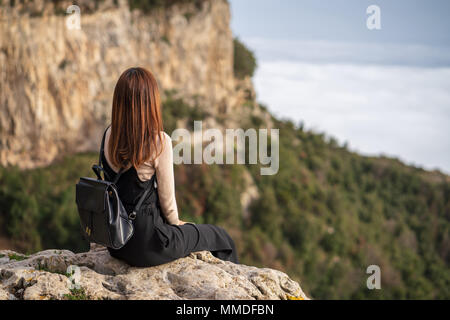 Young woman with black backpack sit on the cliff edge and enjoy the view of mountain landscape while hiking on the mountain in Positano, Italy. - Stock Photo