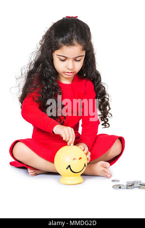 One Little Girl Sitting Floor Putting Coin Piggy-Bank Save Money - Stock Photo