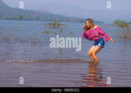 Stylish woman in floral top and denim shorts splashing water in lake - Stock Photo