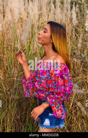 Stylish woman in floral top and denim shorts blowing at blade of grass - Stock Photo