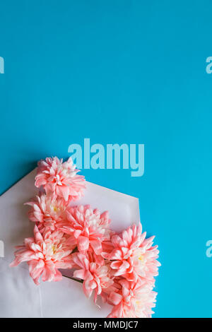Styled feminine flat lay on blue candy background, top view.Minimal woman's desktop with blank page mock up, envelope, pink lisianthus, chrysanthemums. Creative concept, greeting card.Copy space - Stock Photo