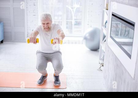 Handsome elderly man holding dumbbells and doing squats