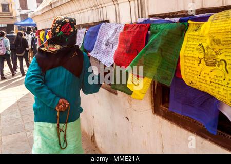 Kathmandu, Nepal - November 22, 2015: Old woman praying around the Boudhanath stupa and turning tibetan prayer wheels. - Stock Photo