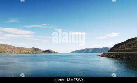 Calm sea inside a Norwegian fjord just north of Olderfjord. Stunning views along the E69 en route to the North Cape. - Stock Photo