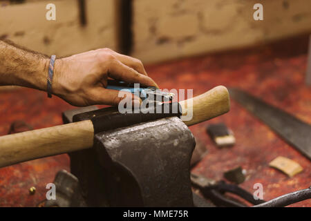 Man working in carpentry workshop. He fastens leather winding on wooden handle of ax. Men at work. Hand work. - Stock Photo