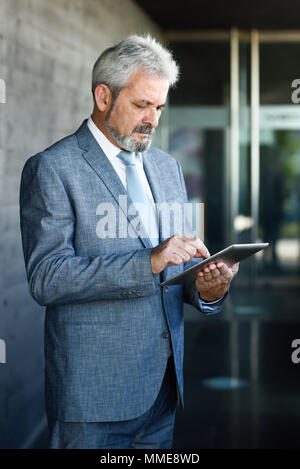Portrait of a senior businessman with tablet computer outside of modern office building. Successful business man in urban background wearing suit and  - Stock Photo