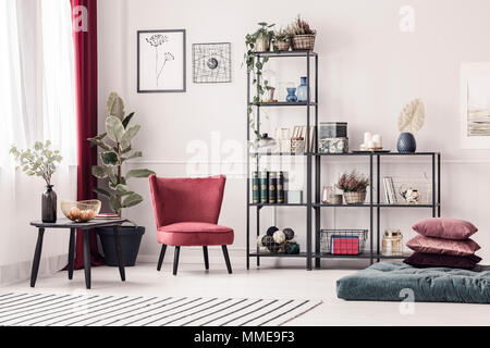 Red, velvet armchair next to a black, metal rack with decorations standing against white wall with molding in bright living room interior - Stock Photo
