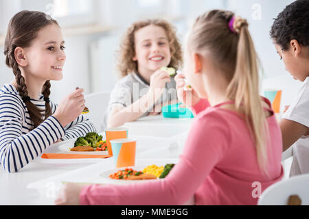 Smiling girl eating vegetables during lunch break with friends at school - Stock Photo