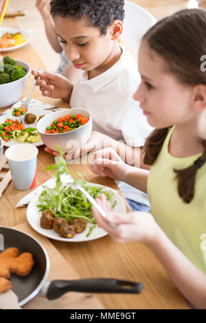 High angle of children eating vegetables for dinner at school - Stock Photo