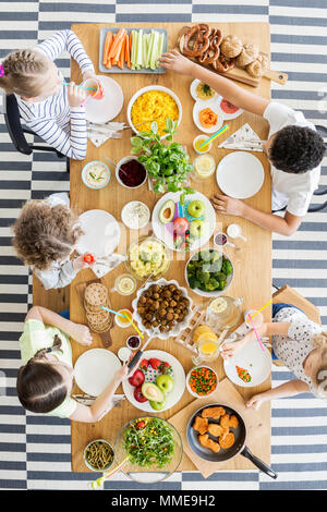 Top view on children eating healthy food at table during birthday party - Stock Photo