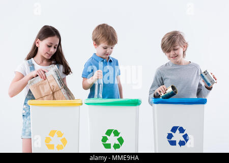 Children segregating paper, glass and metal into yellow, green and blue bins - Stock Photo