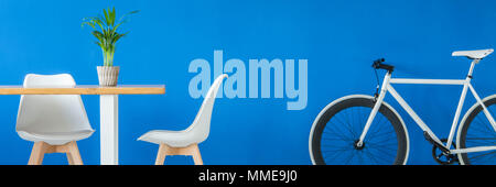 Panorama of a hipster bike by a royal blue wall and a white wooden dining set in a modern apartment interior - Stock Photo