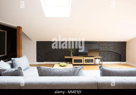 Television on black, brick wall standing in front of a grey couch in modern living room interior