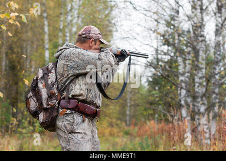 hunter in camouflage taking aim from a hunting gun in the wildfowl - Stock Photo