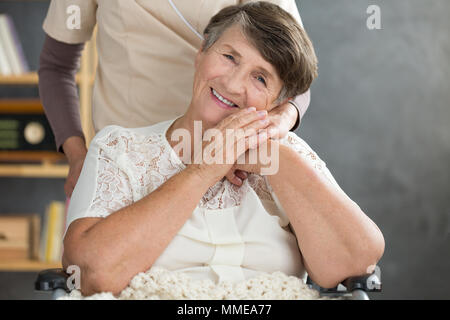Close-up photo of smiling pensioner bonding with her caregiver. Elder support concept. - Stock Photo