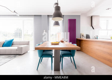Open plan apartment of family living-space with wooden kitchen countertop, purple radiator, communal table with turquoise chairs and spacious living r - Stock Photo